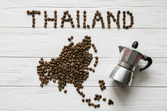 Map of the Thailand made of roasted coffee beans laying on white wooden textured background with coffee maker. Space for text Royalty Free Stock Photography