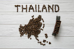 Map of the Thailand made of roasted coffee beans laying on white wooden textured background with toy train. Space for text Royalty Free Stock Photo