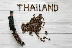 Map of the Thailand made of roasted coffee beans laying on white wooden textured background with toy train. Space for text Royalty Free Stock Images