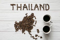 Map of the Thailand made of roasted coffee beans laying on white wooden textured background with two cups of coffee. Space for text Stock Photo