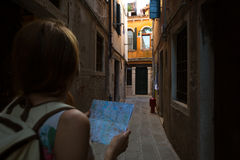 Map. Traveler girl looks at the map of walking in Venice, Italy Royalty Free Stock Photos