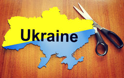 Map of Ukraine and scissors. Concept of dividing a country Stock Photos