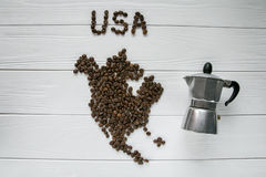 Map of the USA made of roasted coffee beans laying on white wooden textured background with coffee maker. Space for text Royalty Free Stock Images