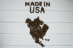 Map of the USA made of roasted coffee beans laying on white wooden textured background. Space for text Stock Image