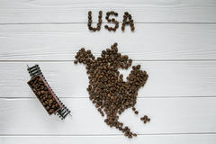Map of the USA made of roasted coffee beans laying on white wooden textured background with toy train. Space for text Stock Images