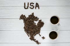 Map of the USA made of roasted coffee beans laying on white wooden textured background with two cups of coffee. Space for text Royalty Free Stock Photos