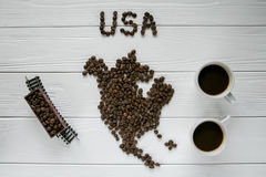 Map of the USA made of roasted coffee beans laying on white wooden textured background with two cups of coffee and toy train. Space for text Stock Photo