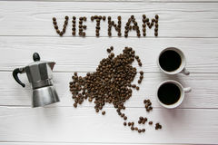 Map of the Vietnam made of roasted coffee beans laying on white wooden textured background with coffee maker and cups of coffee. Space for text Royalty Free Stock Images
