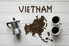 Map of the Vietnam made of roasted coffee beans laying on white wooden textured background with coffee maker and cups of coffee. Space for text Stock Photography