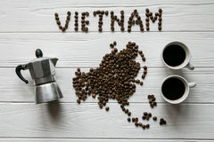 Map of the Vietnam made of roasted coffee beans laying on white wooden textured background with coffee maker and cups of coffee Royalty Free Stock Images