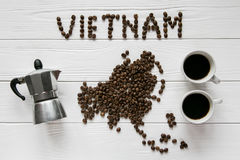 Map of the Vietnam made of roasted coffee beans laying on white wooden textured background with cups of coffee and coffee maker Royalty Free Stock Images