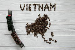 Map of the Vietnam made of roasted coffee beans laying on white wooden textured background with toy train. Space for text Royalty Free Stock Photography