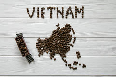 Map of the Vietnam made of roasted coffee beans laying on white wooden textured background with toy train Royalty Free Stock Photography