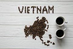 Map of the Vietnam made of roasted coffee beans laying on white wooden textured background with two cups of coffee Stock Photography