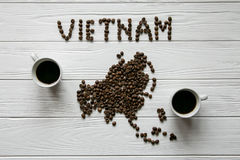 Map of the Vietnam made of roasted coffee beans laying on white wooden textured background with two cups of coffee Royalty Free Stock Images