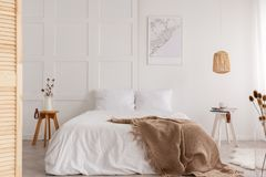 Map on the wall of stylish bedroom interior, real photo. Map on the wall of stylish bedroom interior with big white bed and beige blanket, real photo royalty free stock photos