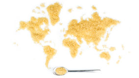 Map of the world made of cane sugar with metallic spoon full of sugar Stock Photography