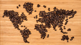 Map of the world made of coffee beans. Map of the world made of roasted arabica coffee beans laying on bamboo wooden textured backgound Stock Photos