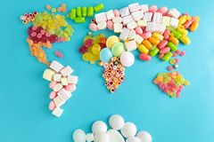 Map of world made from different candies. On blue background stock images