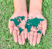 Map of the world in your hands. With green grassy background Stock Photos