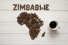 Map of the Zimbabwe made of roasted coffee beans laying on white wooden textured background with coffee maker with cup of cof Stock Images