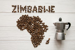 Map of the Zimbabwe made of roasted coffee beans laying on white wooden textured background with coffee maker. And space for text Stock Image