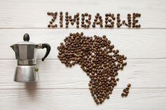 Map of the Zimbabwe made of roasted coffee beans laying on white wooden textured background with coffee maker. And space for text Royalty Free Stock Photo