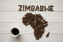 Map of the Zimbabwe made of roasted coffee beans laying on white wooden textured background with cup of coffee. And space for text Royalty Free Stock Photography