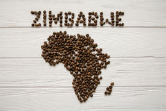 Map of the Zimbabwe made of roasted coffee beans laying on white wooden textured background. And space for text Stock Photos