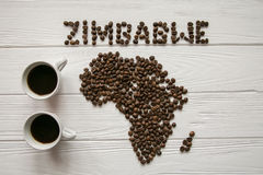 Map of the Zimbabwe made of roasted coffee beans laying on white wooden textured background with two cups of coffee. And space for text Royalty Free Stock Photo
