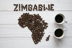 Map of the Zimbabwe made of roasted coffee beans laying on white wooden textured background with two cups of coffee. And space for text Stock Images