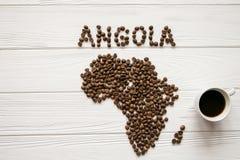 Mapa Angola robić piec kawowe fasole kłaść na białym drewnianym textured tle z filiżanką kawy Zdjęcia Royalty Free
