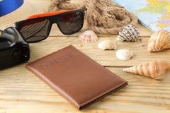 Mapa, cámara, pasaporte, y vidrios del concepto A del viaje, cáscaras en una tabla de madera natural Relajación holidays imágenes de archivo libres de regalías
