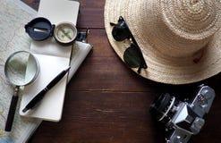 Mapa, cuaderno, cámara y sombrero del viaje en un escritorio fotografía de archivo
