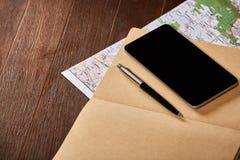Mapa, cuaderno, pluma y teléfono negro en el fondo de madera marrón Imagen de archivo libre de regalías