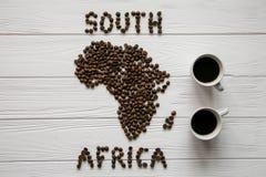 Mapa da África do Sul feita dos feijões de café roasted que colocam no fundo textured de madeira branco com duas xícaras de café Fotografia de Stock Royalty Free