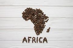 Mapa da África feita dos feijões de café roasted que colocam no fundo textured de madeira branco Fotos de Stock Royalty Free
