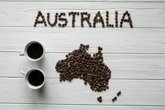 Mapa da Austrália feita dos feijões de café roasted que colocam no fundo textured de madeira branco com os dois copos de café Fotografia de Stock Royalty Free