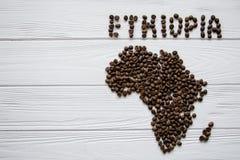 Mapa da Etiópia feita dos feijões de café roasted que colocam no fundo textured de madeira branco Imagens de Stock Royalty Free