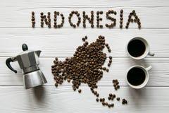 Mapa da Indonésia feita dos feijões de café roasted que colocam no fundo textured de madeira branco com xícaras de café e fabrica Imagens de Stock Royalty Free