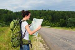 Mapa da leitura do caminhante da mulher Fotos de Stock Royalty Free