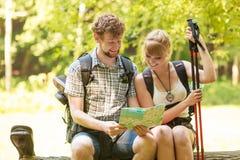 Mapa da leitura dos pares dos mochileiros dos caminhantes na viagem fotografia de stock royalty free