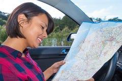 Mapa de camino de la lectura de la mujer en coche al aire libre fotografía de archivo