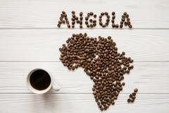 Mapa de la Angola hecha de los granos de café asados que ponen en el fondo texturizado de madera blanco con la taza de café imagen de archivo