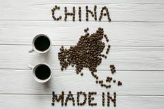 Mapa de la China hecha de los granos de café asados que ponen en las tazas texturizadas de madera blancas del fondo de café Foto de archivo libre de regalías
