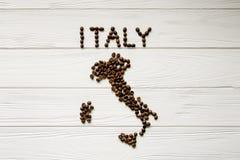 Mapa de la Italia hecha de los granos de café asados que ponen en el fondo texturizado de madera blanco imagen de archivo