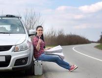 Mapa de la lectura de la mujer al lado del coche Imagen de archivo