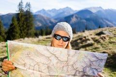 Mapa de la lectura del caminante de la mujer en montañas imagen de archivo libre de regalías