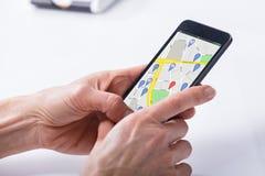 Mapa de la navegación GPS de Person Using en el teléfono móvil fotos de archivo