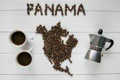 Mapa de la Panamá hecha de los granos de café asados que ponen en el fondo texturizado de madera blanco con las tazas de café y d imagen de archivo libre de regalías